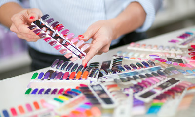 Woman choosing colorful artificial nails at beauty store, closeup