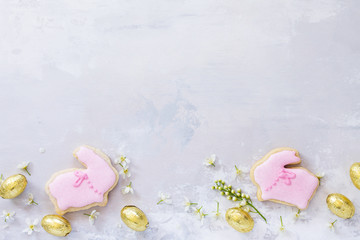 Spring concept. Colorful Easter background with colored eggs and Easter baking on a gray stone background with copy space. Flat lay. Top view with copy space.