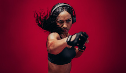 Boxer practicing her punches in a studio