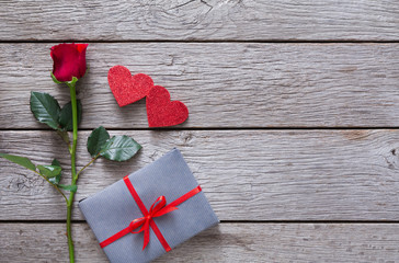 Valentine background with red rose flower, paper hearts and present box on rustic wood