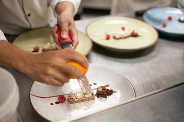 blurry background, Dessert with chef slide orange peel on top in the restaurant kitchen.
