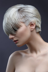 Fashion beauty portrait of a blonde girl with a stylish short haircut, bangs closes her eyes.