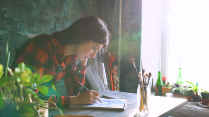 Young woman artist painting sketch on paper notebook with pencil. Bright sun flare from window