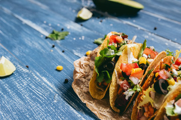 Mexican tacos with vegetables on the wooden blue background, close up.