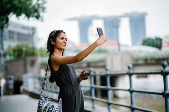 Portrait of young Indian lady taking selfie along a river