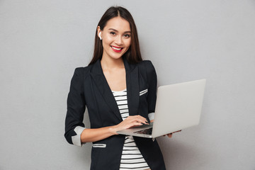 Happy business woman holding laptop computer and looking at camera
