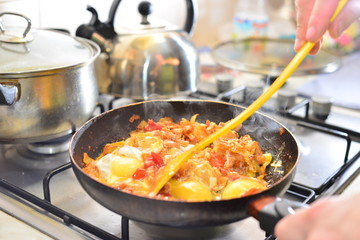 Fried eggs and sweet potato hash in cast iron skillet sitting on red striped kitchen towel
