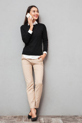 Full length image of Smiling asian woman in business clothes