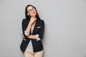Picture of Pensive asian business woman in eyeglasses looking up