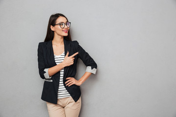 Smiling asian business woman in eyeglasses with arm on hip