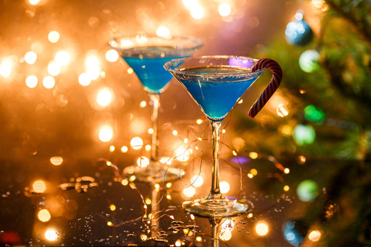 Christmas picture of two wine glasses with blue cocktail and garland