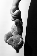 Black and white photo of a girl holding a teddy bear