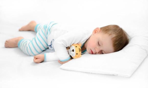 Sleeping baby on white background. Toddler boy in pijama sleeps on white pillow under blanket