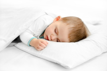 Sleeping baby on white background. Toddler boy in pijama sleeps on white pillow