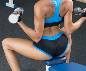 Active woman sitting back in the sportswear and deals with a dumbbell in the gym. Legs apart. Beautiful body. Shiny skin.