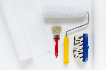 house repair equipment, white wallpaper roll with paint roller and brush