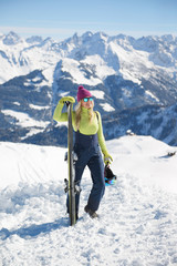 Young blonde woman with ski in the mountains at the sunny day