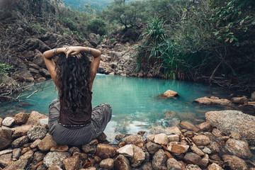 young woman sitting by the lake in jungles