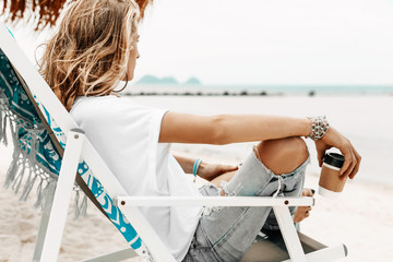stylish young beautiful woman in casual wear relaxing in chair on the tropical beach