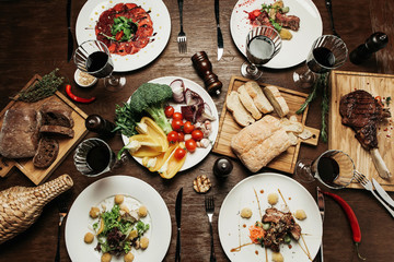 beautifully laid wooden table with different dishes: with carpaccio of beef, salad with pear, different types of meat, with a bread board and vegetables