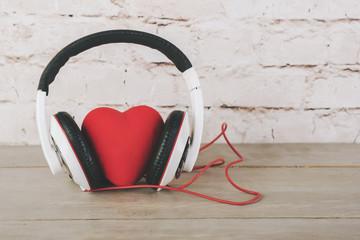 San Valentín, corazón con auriculares sobre una mesa de madera