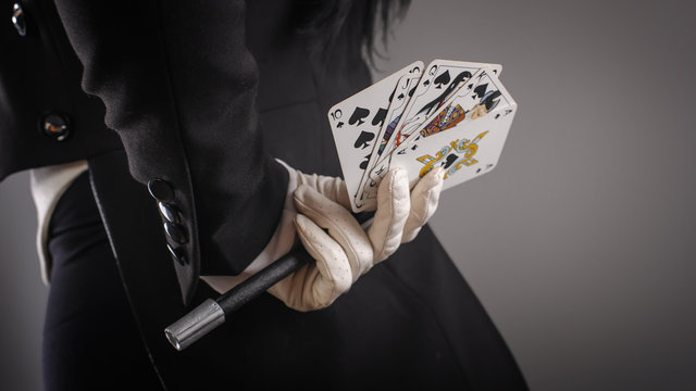 Magic wand and cards in hands of female magician. Closeup