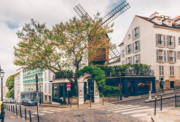 View of cozy street with old mill in quarter Montmartre in Paris, France
