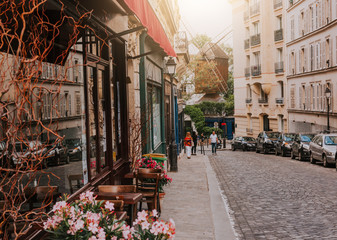 Cozy street with tables of cafe and old mill in quarter Montmartre in Paris, France