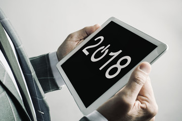 man and number 2018, as the new year, in a tablet