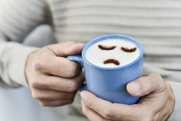 man with a cup of cappuccino with a sad face