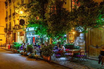 Cozy street with tables of cafe in Paris at night, France