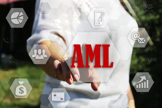 The businesswoman chooses the AML, Anti-money laundering on a touch screen. Business Concept AML