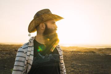 Bearded man in hat against sunlight