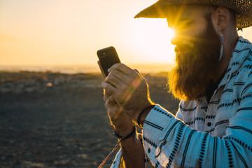 Bearded man in hat browsing smartphone