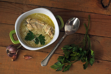 Chicken noodle soup in a ceramic bowl, garlic and greens on a wooden table. Top view.