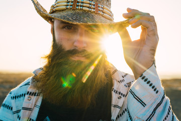 Bearded man in hat against sunlight