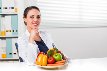 Female dietician showing vegetables and fruit