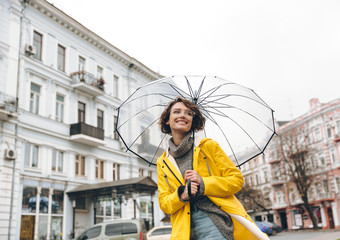 Optimistic woman in yellow raincoat and glasses having fun while walking through city under big transparent umbrella during cold rainy day