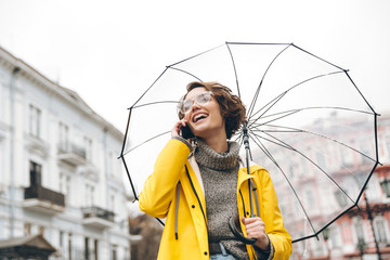 Shot of young woman in yellow raincoat and glasses talking on mobile phone having pleasant conversation under umbrella