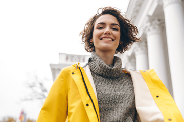 Closeup portrait of charming young woman with bob haircut enjoying walk through the city in yellow coat smiling on camera