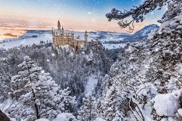 Neuschwanstein Castle during sunrise in winter landscape.