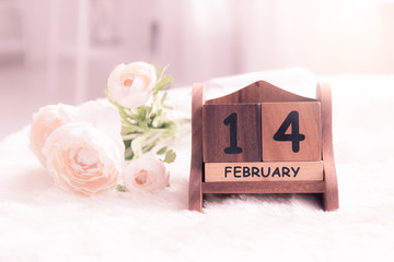 Pink roses lay on the table near calendar with the date of February 14,Valentine's day concept