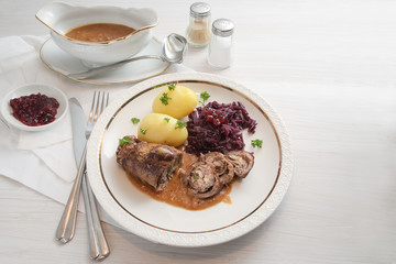 beef roulade with red cabbage, potatoes and sauce, german meat roll stuffed with cucumbers, bacon and onions on a white plate on a light wooden table, copy space, selected focus