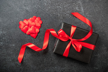 Gift box and heart decoration on black background