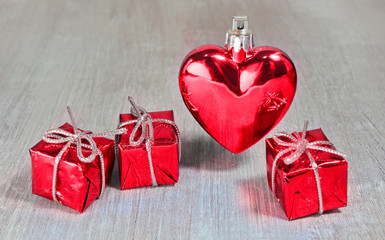 Red valentine or christmas heart and gifts on white wooden background
