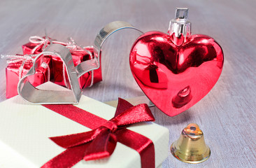 Red valentine or christmas heart and gifts with small jingle and steel hearts on white wooden background