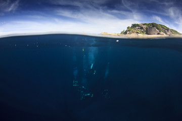 Wall Mural - Scuba divers underwater half and half split over under photo