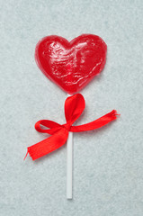 A heart shape lollipop with a red ribbon tied to the stick part