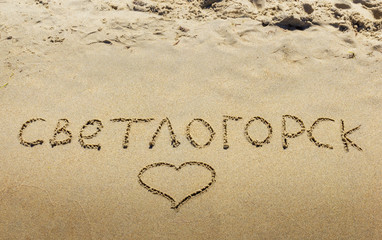 Inscription on wet sand Svetlogorsk . Russia.
