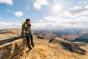 young woman traveler sits on the edge of the cliff, enjoys nature and the sun